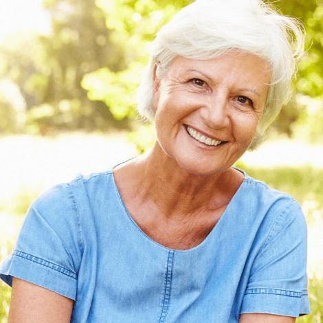 A smiling, older woman after getting dentures.
