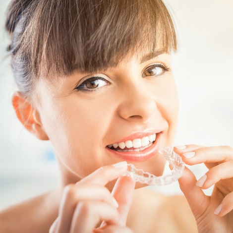 Young woman putting Invisalign aligner tray into her mouth.