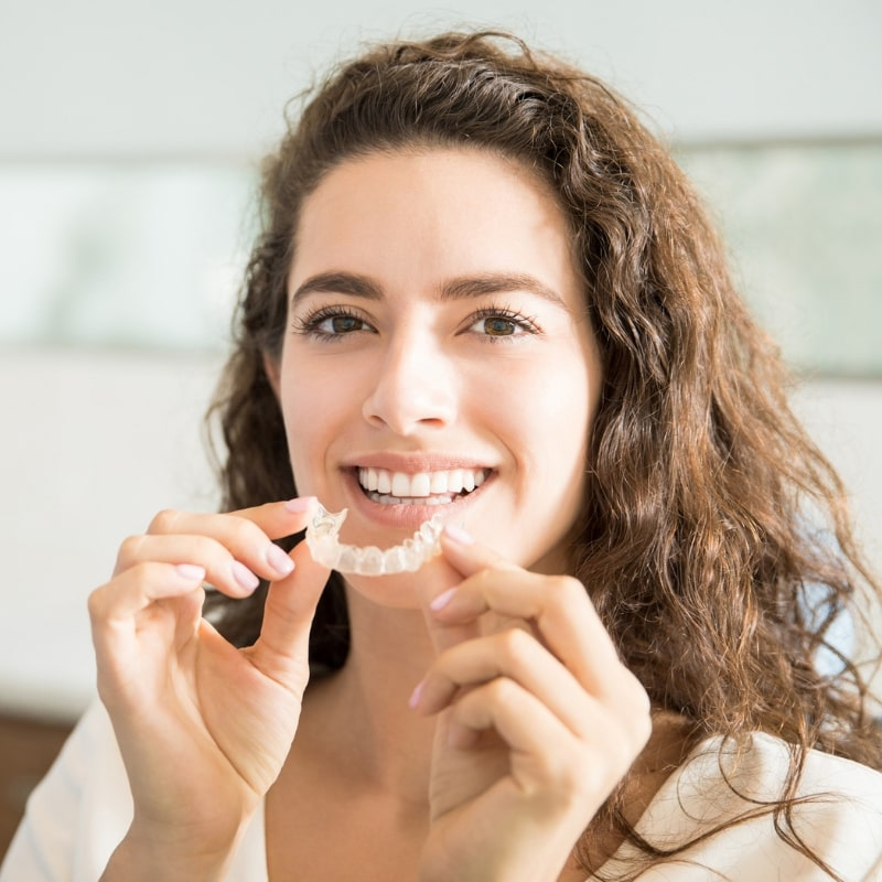 Woman with long brown hair placing Invisalign aligner tray into her mouth.