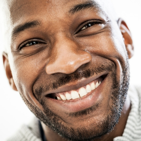 Close-up shot of smiling man with facial hair.