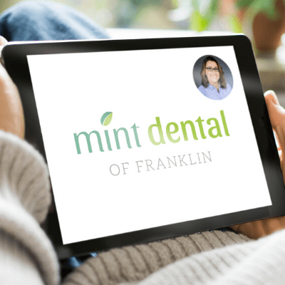 Person holding an ipad for their dental virtual consultation with Mint Dental's logo and picture of our dentist